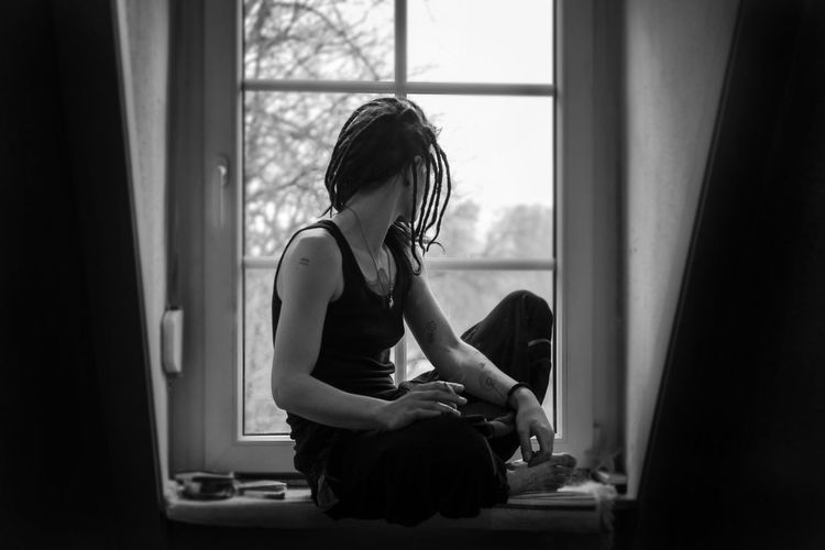 Thoughtful Young Woman Sitting On Window Sill At Home