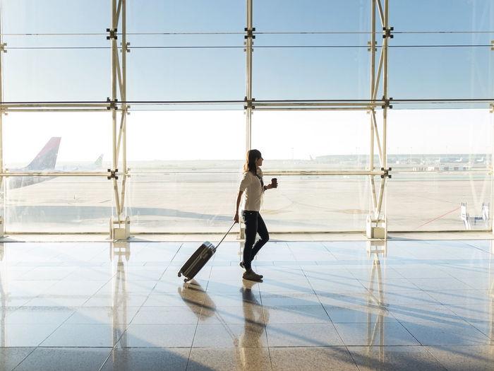 Side view of man walking on glass window