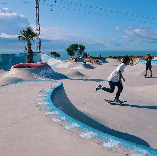 People on skateboard park against sky