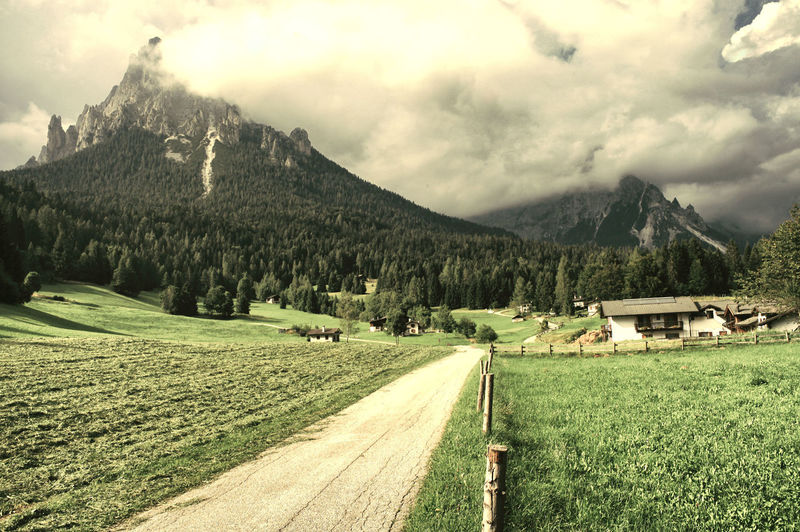 Glade with dramatic mountains in the background Dolomites, Italy Colors Light And Shadow Light Sunlight Street Sunset Reflection EyeEm Selects Color Cloud - Sky Mountain House Village Tree Mountain Rural Scene Agriculture Field Sky Landscape Grass Mountain Range Cloud - Sky Cultivated Land