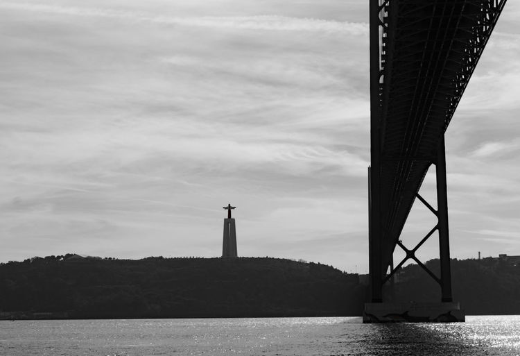 Statue and bridge over sea against cloudy sky