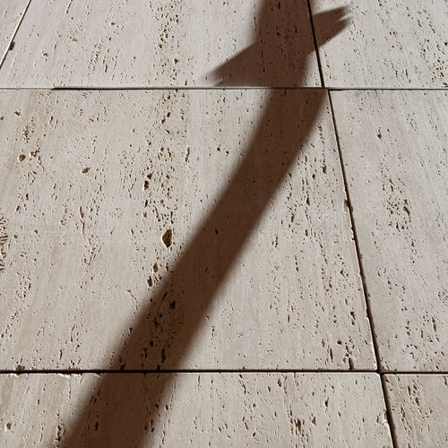 Shadow of wall on tiled floor
