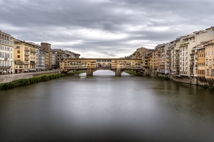 Ponte vecchio over river in city against sky