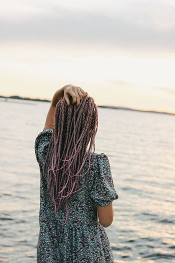 Rear view of woman with hand in hair standing at beach against sky