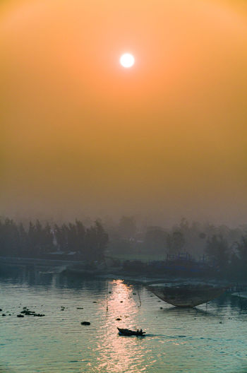 Beauty In Nature Fog Idyllic Mode Of Transportation Nature Nautical Vessel No People Non-urban Scene Orange Color Outdoors Scenics - Nature Sea Sky Sun Sunset Tranquil Scene Tranquility Transportation Tree Water Waterfront