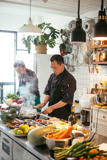 Adult Business Chef Food Food And Drink Freshness Indoors  Kitchen Men Mid Adult Mid Adult Men Occupation People Preparation  Preparing Food Real People Restaurant Standing Two People Vegetable Waist Up
