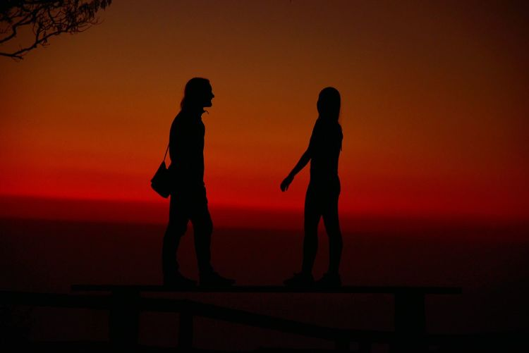 Silhouette people standing against orange sky during sunset