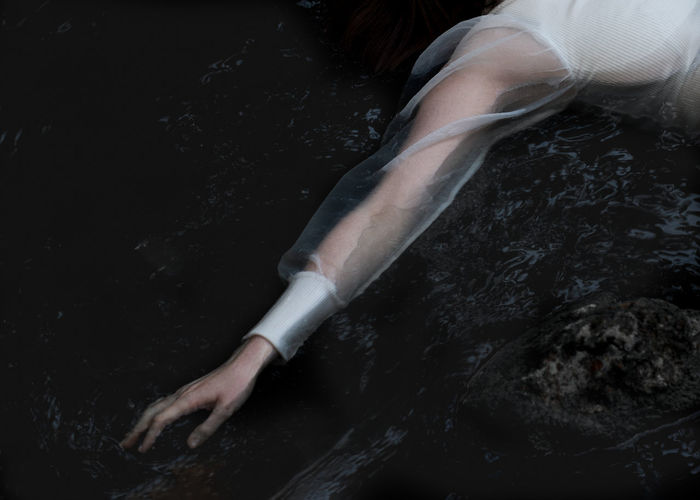 Low section of woman swimming in water