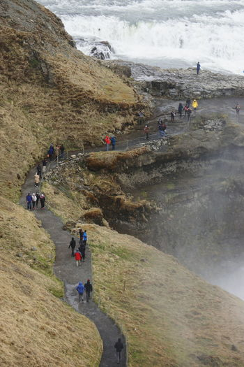High Angle View Of People Standing On Footpath By Mountain At Gullfoss Waterfall
