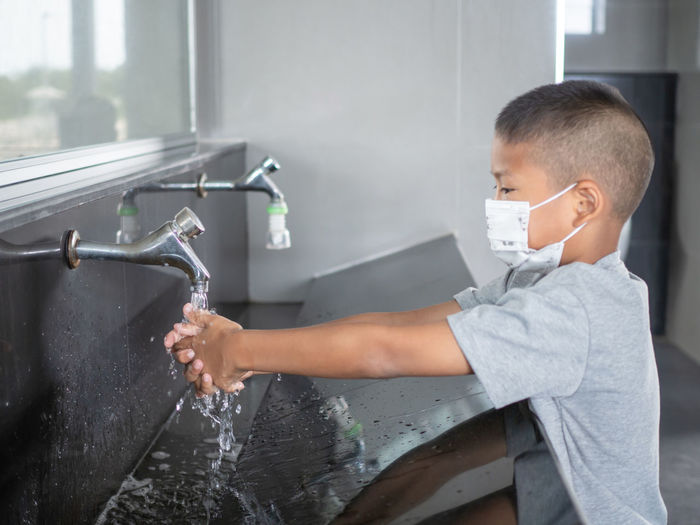 Boy washing hands from faucet in bathroom