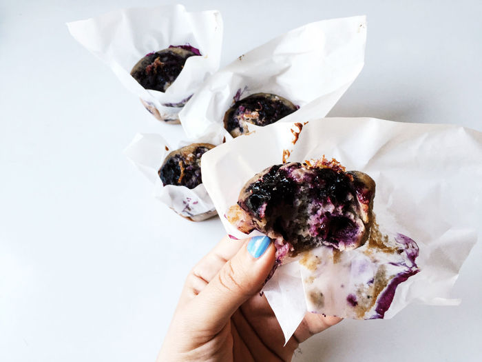 Cropped Image Of Woman Holding Blueberry Muffin At Table