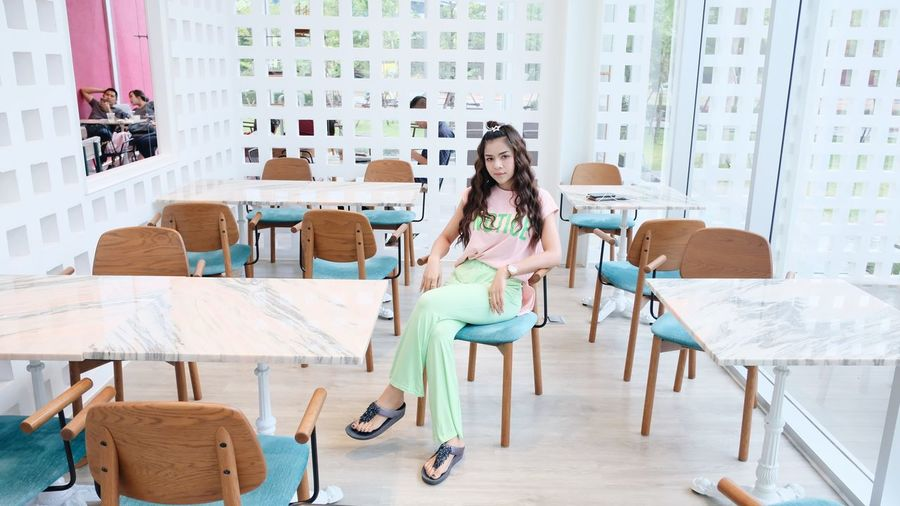 Portrait of young woman sitting on table in cafe