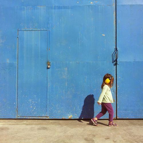 Woman standing against blue door