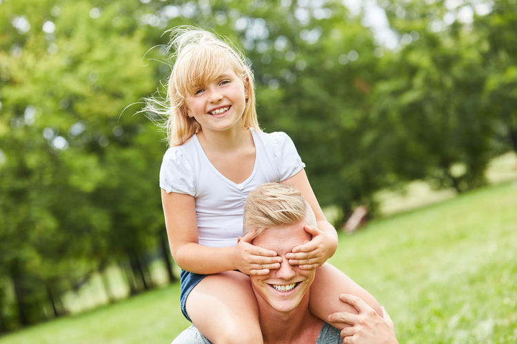 Portrait Of Smiling Daughter Covering Eyes Of Father On Field