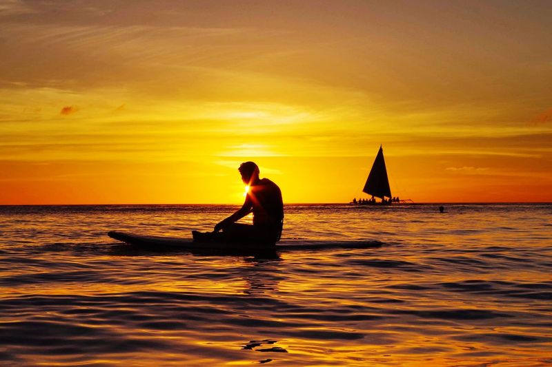 Silhouette Man Sitting On Surfboard In Sea During Sunset