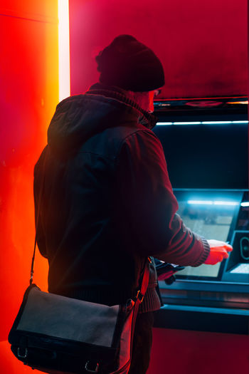 Man at the atm machine for withdrawing money in a cold winter night