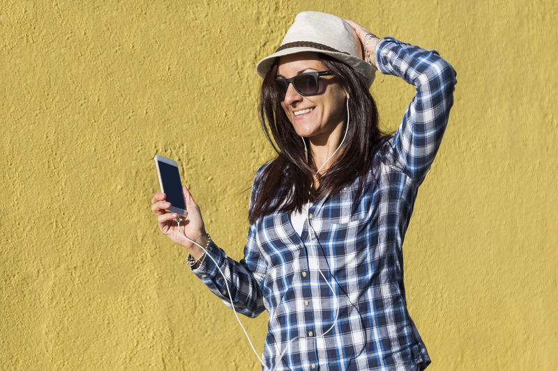 Portrait of smiling young man using smart phone against yellow wall
