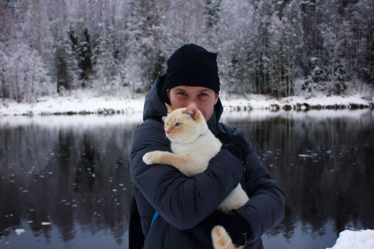 Portrait of young man carrying cat while standing against lake in forest