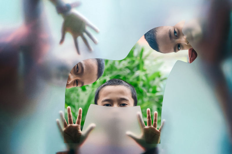 Portrait of boys looking through glass