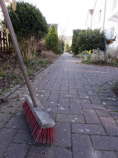 A street broom with rough red long bristles and wooden handle Broom Stick Handle Wooden Red Color Bristles Outdoors No People Day Outside Garden Photography Garden Tools Housekeeping Cleaning Cleaning Equipment Object Broomstick Brush Dirty Footpath Plant Tree Architecture Nature Built Structure Empty Sidewalk Paving Stone The Way Forward Absence Park Street Stone