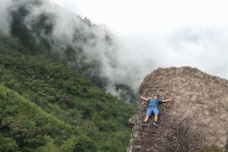 High Angle View Of Hiker Relaxing On Mountain During Foggy Weather