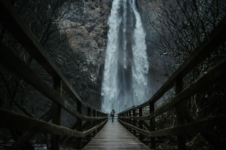 Distant view of man walking on footbridge towards waterfall