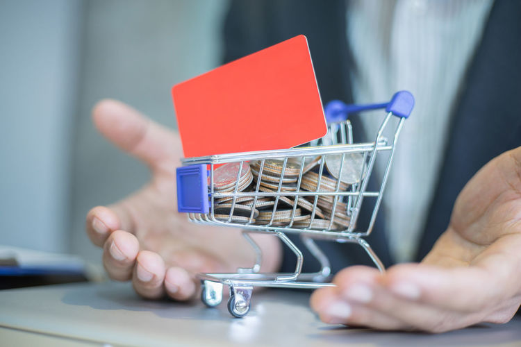 Close-Up Midsection Of Businessman With Coins In Cart On Table At Office