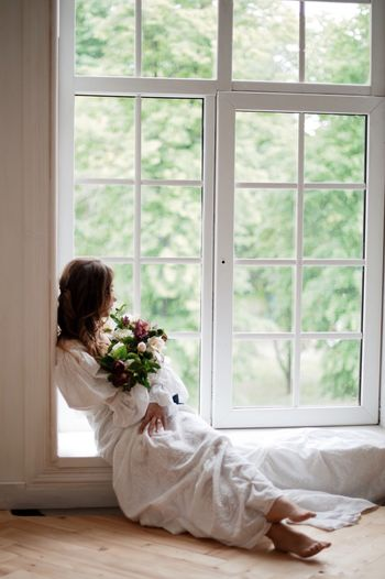 Young Woman Sitting With Flowers On Window At Home