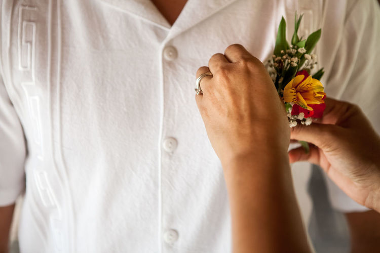 Cropped hand of woman adjusting flowers in man shirt