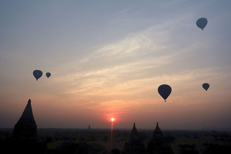 Hot air balloons flying in sky during sunset