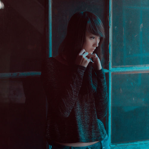 Thoughtful young woman standing against window