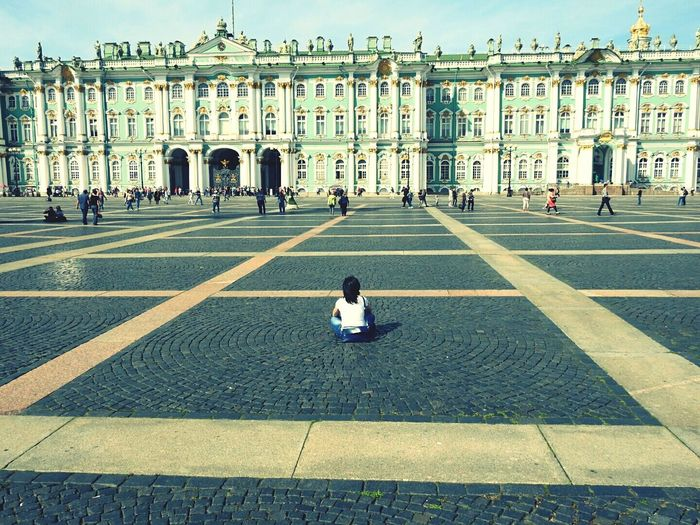 Rear view of woman sitting at palace square