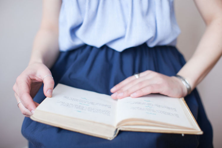 Midsection of woman with book