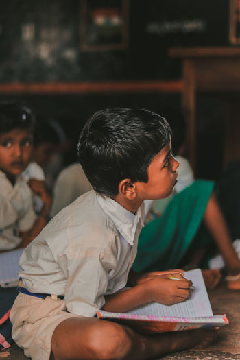Side view of boy studying while sitting at school