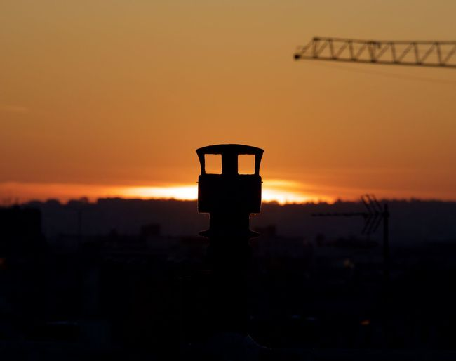 Silhouette of communications tower against sunset sky