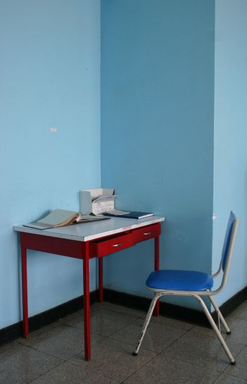 Table And Chair Against Blue Wall