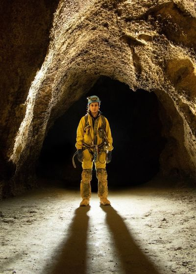 Full Length Of Miner Standing In Cave