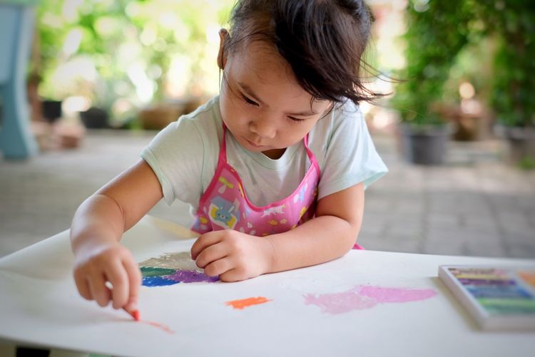 Cute girl coloring on table