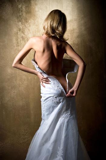 Woman opening zipper of dress against wall