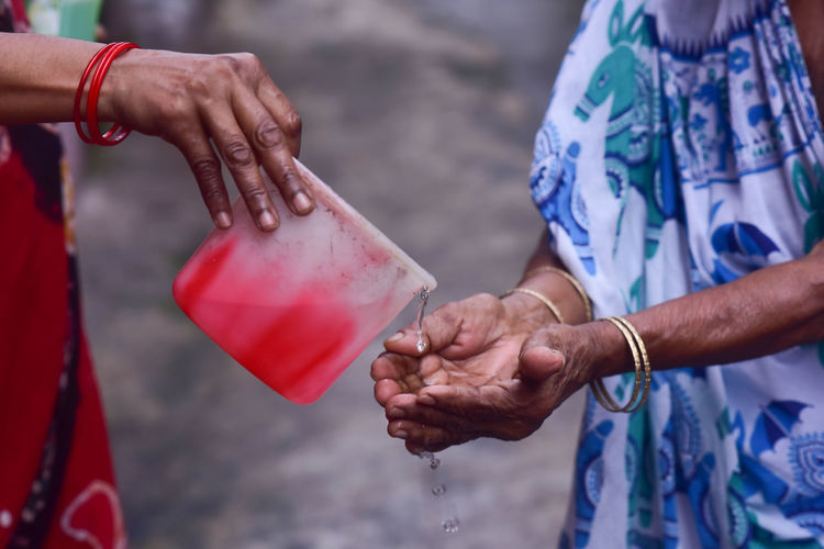 Cropped image of hand pouring water on woman hand