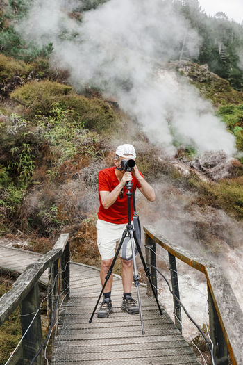 Man photographing with camera while standing on boardwalk against mountain