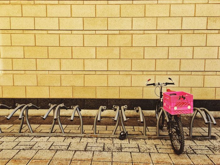 Wall - Building Feature Bicycle Transportation Land Vehicle Mode Of Transport No People Outdoors Brick Wall Building Exterior Bicycle Rack Stationary Built Structure Architecture Day Pink Color Millennial Pink