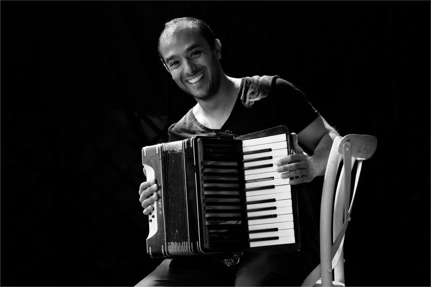 Musician Music One Person Accordion Arts Culture And Entertainment Musical Instrument Front View Musical Equipment Musician Playing Indoors  Young Adult Artist Real People Studio Shot Young Men Stage Leisure Activity Black Background Holding Men