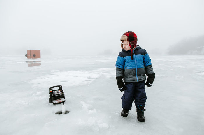 Ice Fishing Beauty In Nature Boys Childhood Cold Temperature Day Front View Full Length Minnows Nature One Boy Only Outdoors People Portrait Real People Sky Snow Standing Warm Clothing Weather Winter