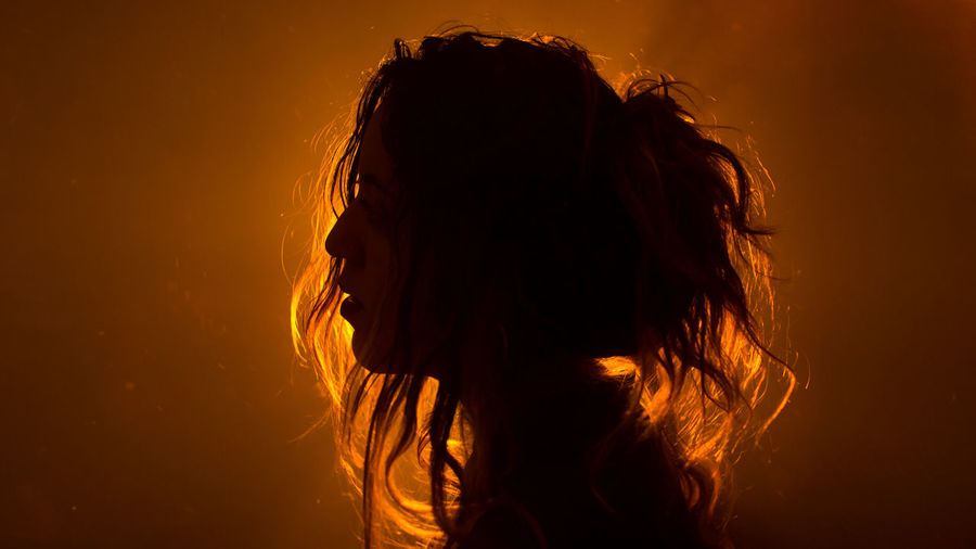 Close-up of silhouette woman against gray background