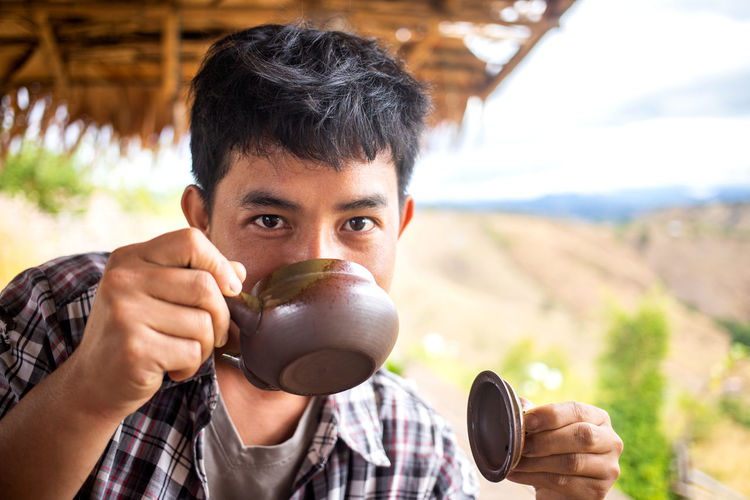 Man smelling tea from the teapot Portrait Holding Headshot One Person Men Adult Young Adult Outdoors Photographer Nature Teatime Tea Teapot Smelling Good Smell Young Men Thailand Thai ASIA North Thailand Nan Pua Lanna Hill Mountain