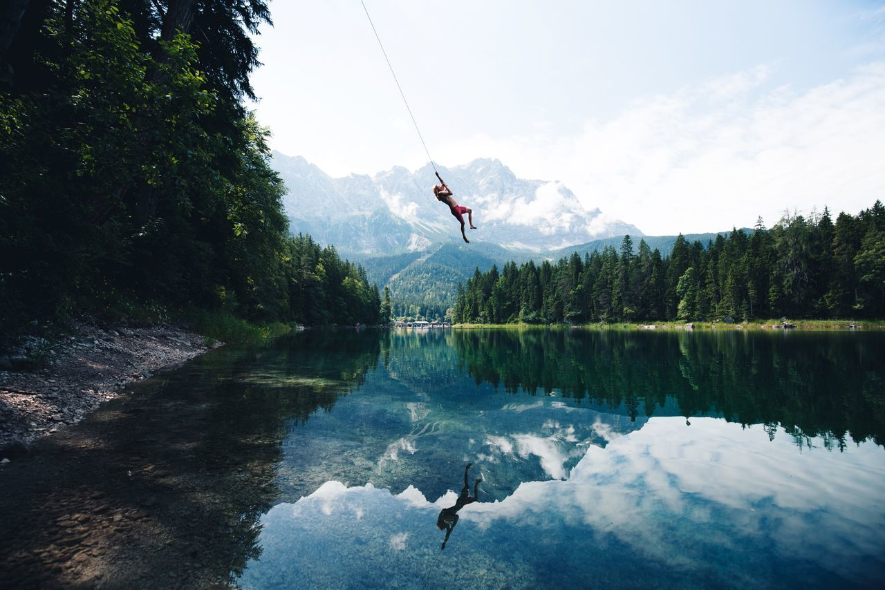 WOMAN PARAGLIDING OVER LAKE AGAINST TREES