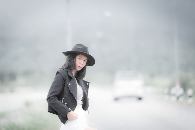 Portrait Of Mid Adult Woman Wearing Hat And Leather Jacket Standing On Road