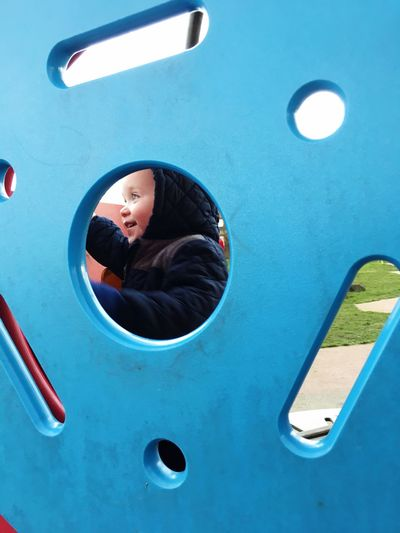 Happy toddler boy seen from blue play equipment at playground