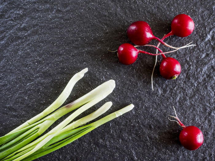 Directly above shot of radishes by scallions on slate